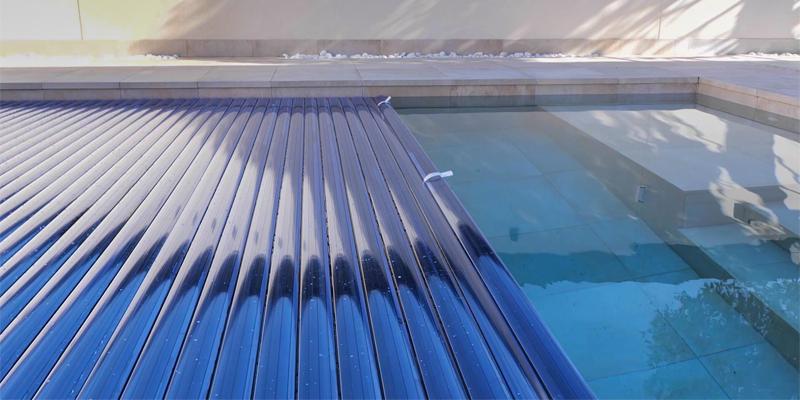 primer plano de cubierta de lamas en color azul flotando sobre el agua de la piscina